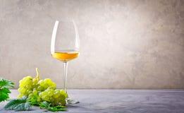 一杯白葡萄酒和一束葡萄 免版税库存图片