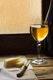 一杯白葡萄酒用在一块亚麻制毛巾的乳酪在木桌上 库存图片