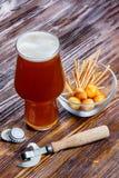 一杯的构成与泡沫的啤酒在一个碗的一张土气木桌上咸快餐和瓶盖启子旁边 免版税图库摄影