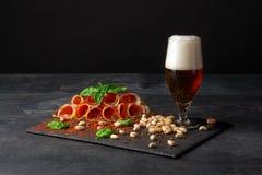 一杯的特写镜头啤酒 与各种各样的快餐的酒精啤酒在黑背景 咸坚果,辣火腿切片 图库摄影