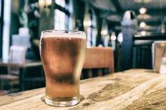 一杯的特写镜头在一张桌上的新鲜的泡沫似的啤酒在葡萄酒b 库存照片