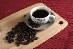 一杯粗粒咖啡在和咖啡豆 库存图片