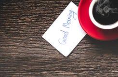 一杯红色咖啡与在老木桌写早晨好 免版税图库摄影