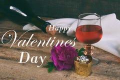 一杯红葡萄酒,瓶和在土气木桌上上升了 华伦泰` s天静物画 概念与题字的贺卡 免版税图库摄影