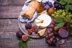 一杯红葡萄酒,葡萄,乳酪,黄柏,拔塞螺旋,在黑暗的背景的白面包 免版税库存照片