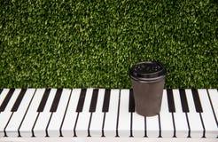 一杯纸咖啡在一架钢琴的钥匙的立场在绿色象草的背景的 库存图片