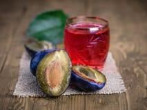 一杯自创李子开胃酒用蓝色李子新鲜的莓果在vitage桌上的 库存照片