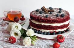 一杯自创蛋糕anda玻璃茶用精美乳脂状的花、蓝莓、臀部和桂香装饰的鞋带表面上的 免版税图库摄影