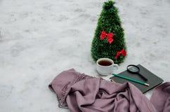 一杯茶、围巾、放大镜、铅笔、笔记本和一棵小人为圣诞树 图库摄影