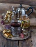 一杯茶、糖煮的烤坚果和日期在Th桌上  免版税库存图片