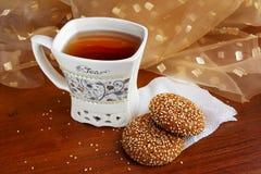 一杯茶与可口甜点的在桌上 库存图片