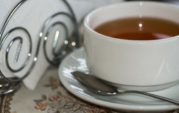 一杯茶与茶碟和匙子,在一张桌上的一系列的餐巾的在咖啡馆, 免版税图库摄影