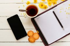一杯茶和与笔的一个笔记薄 免版税库存图片