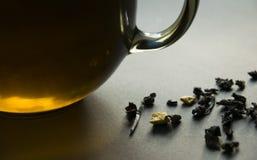 一杯茶和疏散茶叶在黑暗的背景 库存照片