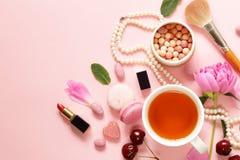 一杯茶妇女、蛋白杏仁饼干、花和甜点的 库存图片