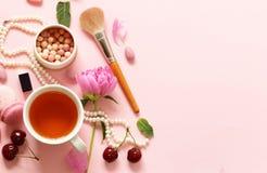 一杯茶妇女、蛋白杏仁饼干、花和甜点的 免版税库存图片