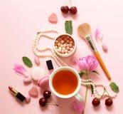 一杯茶妇女、蛋白杏仁饼干、花和甜点的 库存照片