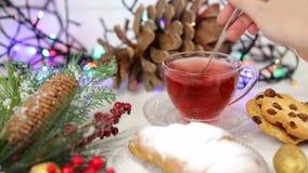 一杯茶用蜂蜜和新月形面包,一棵圣诞树的分支在雪,圣诞灯的 股票录像