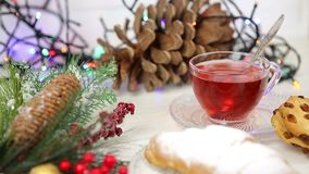 一杯茶用蜂蜜和新月形面包,一棵圣诞树的分支在雪,圣诞灯的 股票视频