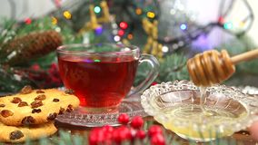 一杯茶用蜂蜜和曲奇饼,一棵圣诞树的分支在雪,圣诞灯的 股票录像