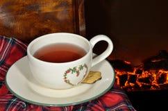 一杯茶由壁炉的 库存照片