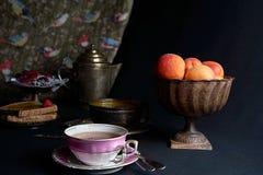 一杯茶由新鲜的杏子、杏子果酱和莓果盘子伴随 图库摄影