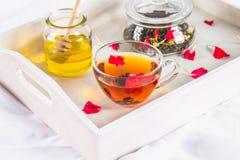 一杯茶,一个罐蜂蜜和一个瓶子在一个白色盘子的黑清凉茶在床上 免版税库存图片
