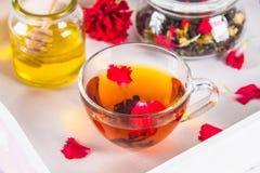 一杯茶,一个罐蜂蜜和一个瓶子在a的黑清凉茶 库存照片