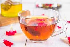 一杯茶,在蜂蜜和瓶子机智银行的背景中  库存照片
