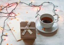 一杯茶,有光的圣诞节诗歌选和在轻的背景的一个礼物盒 圣诞节礼物 库存照片