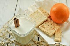 一杯酸奶、酥皮点心和新鲜水果轻的表面上 库存图片