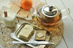 一杯酸奶、黄油、一个罐茶,酥皮点心和新鲜水果轻的表面上 图库摄影