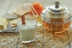 一杯酸奶、黄油、一个罐茶,酥皮点心和新鲜水果轻的表面上 库存照片