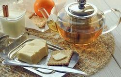 一杯酸奶、黄油、一个罐茶,酥皮点心和新鲜水果轻的表面上 免版税图库摄影