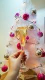 一杯闪耀的香槟在手中在装饰的白色树背景  库存图片