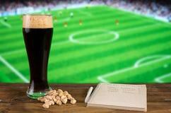 一杯黑啤酒,与笔记薄的pistachioson在橄榄球场背景  复制空间 免版税库存照片