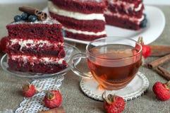 一杯玻璃茶和亚麻制表面上的一个美丽的自创蛋糕装饰用蓝莓、臀部、鞋带和肉桂条 免版税库存照片