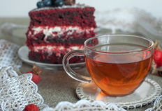 一杯玻璃茶和亚麻制表面上的一个美丽的自创蛋糕装饰用蓝莓、臀部、鞋带和肉桂条 库存图片