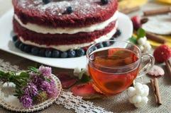 一杯玻璃茶和亚麻制表面上的一个美丽的自创蛋糕装饰用蓝莓、臀部和肉桂条 免版税库存照片
