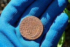 一枚大老铜币在一只手的棕榈说谎在一副蓝色手套的 免版税图库摄影