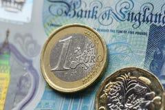 一枚欧洲硬币和一1英镑硬币在英国五磅笔记以一个横向格式 库存图片