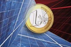 一枚欧洲硬币和太阳电池板反对红色背景,关闭 免版税库存图片