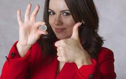 一枚欧洲硬币在一个少妇的手上 库存图片