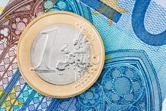 一枚欧洲硬币细节在蓝色钞票背景的 库存图片