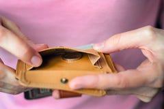 一枚硬币在一个空的钱包里在妇女` s手上 库存图片