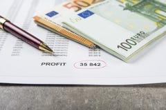 一枚笔、计算器和硬币的企业经营情况的概念图象在财政文件 免版税库存照片
