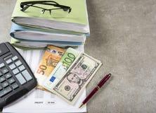 一枚笔、计算器和硬币的企业经营情况的概念图象在财政文件 库存照片