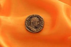 一枚老硬币的图片在黄色织品的 免版税库存照片