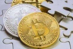 一枚金黄和银色bitcoin硬币的精选的焦点关闭 Cryptocurrency 缺掉七巧板片断 到达天空的企业概念金黄回归键所有权 免版税库存照片