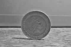 一枚银色和金黄硬币的宏观细节与女王/王后头的按两英磅2的价值木表面上的GBP 免版税图库摄影